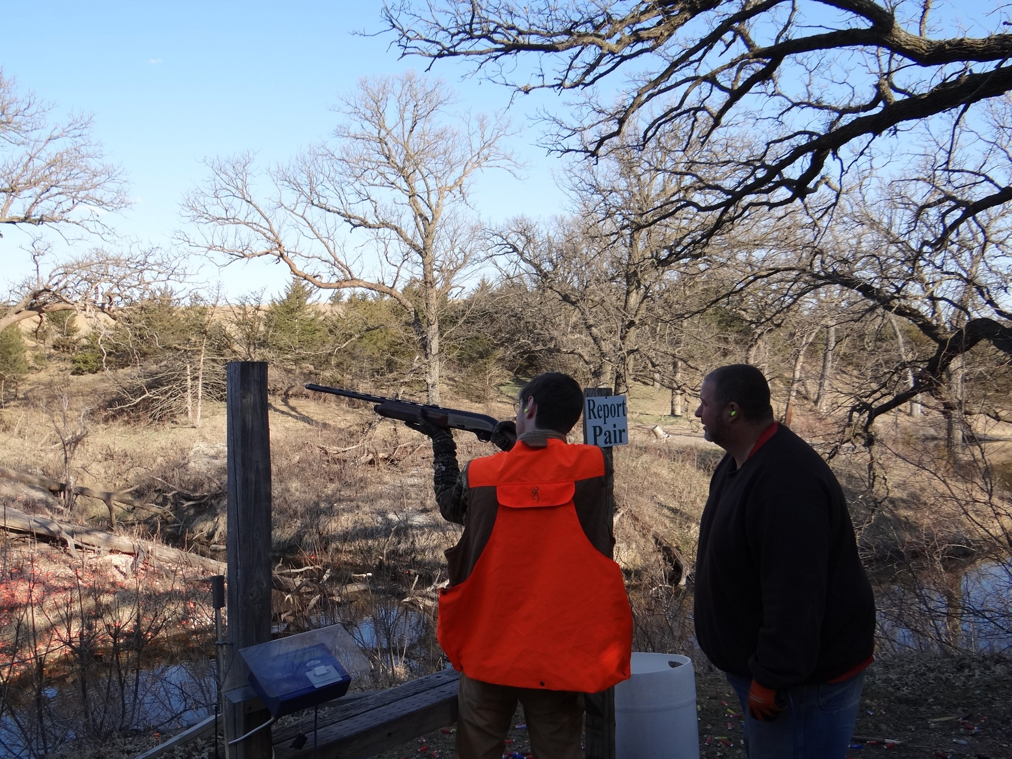 Noah shoots sporting clays at Oak Creek Sporting Club under the watchful eyes of Terry Kriz. Photo by Greg Wagner.